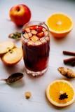Καυτό θερμαμένο κρασί σε ένα γυαλί με τις πορτοκαλιά φέτες, το γλυκάνισο και τα ραβδιά κανέλας, μπισκότα αστεριών στον εκλεκτής π Στοκ εικόνες με δικαίωμα ελεύθερης χρήσης