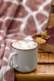 Καυτό κακάο με marshmallow στο υπόβαθρο ενός καρό και ενός βιβλίου Στοκ εικόνα με δικαίωμα ελεύθερης χρήσης