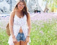 καυτό καλοκαίρι Απίστευτο πορτρέτο ενός κοριτσιού στα σορτς ελαφριών άσπρων φορεμάτων και τζιν που θέτουν σε ένα καυτό απόγευμα Στοκ Εικόνες