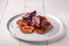 καυτό κρέας πιάτων Πλευρά χοιρινού κρέατος που ψήνονται στη σχάρα με τα πιπέρια και τα μήλα Στοκ Εικόνες