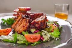 καυτό κρέας πιάτων Πλευρά χοιρινού κρέατος που ψήνονται στη σχάρα με τη σαλάτα και τα μήλα σε ένα πιάτο Στοκ Εικόνα