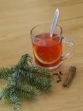 Καυτό κόκκινο τσάι με τα γαρίφαλα κανέλας λεμονιών με το ασημένιο κομψό δέντρο β στοκ εικόνα