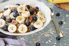 Καυτό κύπελλο Oatmeal των μπανανών και των βακκινίων στοκ εικόνα