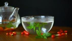 Καυτό τσάι από τα ώριμα κόκκινα μούρα goji teapot γυαλιού απόθεμα βίντεο