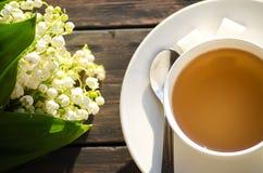 Καυτό τσάι σε ένα άσπρο φλυτζάνι με μια ανθοδέσμη των λουλουδιών Στοκ εικόνες με δικαίωμα ελεύθερης χρήσης