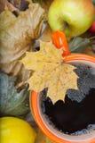 Καυτό τσάι σε ένα πορτοκαλί φλυτζάνι στα ξηρά φύλλα Στοκ Εικόνα