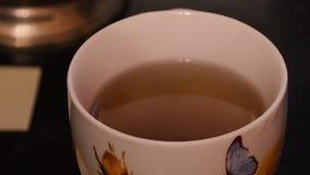 Καυτό τσάι σε μια κινηματογράφηση σε πρώτο πλάνο κουπών απόθεμα βίντεο