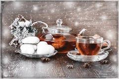 Καυτό τσάι στα Χριστούγεννα στο διαφανές φλυτζάνι γυαλιού με το τσάι, το μελόψωμο, την κανέλα και τη βανίλια Κάρτα με το χιόνι στοκ εικόνα με δικαίωμα ελεύθερης χρήσης