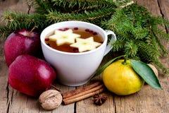 Καυτό τσάι Χριστουγέννων με το ξύλινο φλυτζάνι υποβάθρου κανέλας μούρων της Apple των καυτών κλάδων Horiz του FIR φρούτων υποβάθρ Στοκ Φωτογραφία
