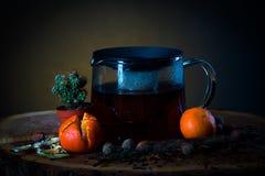 Καυτό τσάι teapot σε έναν ξύλινο πίνακα με τα μανταρίνια και τον κάκτο στοκ φωτογραφία με δικαίωμα ελεύθερης χρήσης