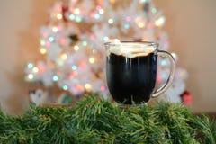 Καυτό φλυτζάνι κακάου που τίθεται μπροστά από το άσπρο χριστουγεννιάτικο δέντρο με τα χρωματισμένα φω'τα στοκ φωτογραφία με δικαίωμα ελεύθερης χρήσης