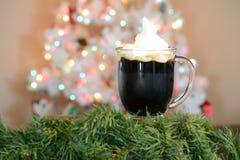 Καυτό φλυτζάνι κακάου που τίθεται μπροστά από το άσπρο χριστουγεννιάτικο δέντρο με τα χρωματισμένα φω'τα στοκ εικόνα με δικαίωμα ελεύθερης χρήσης