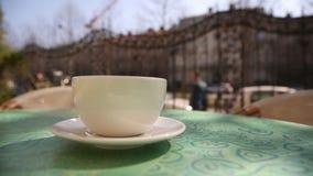 Καυτό φλυτζάνι καφέ με τον ατμό στον πίνακα στον καφέ το πρωί, έξω απόθεμα βίντεο