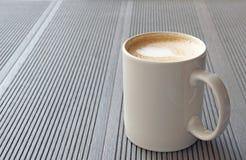 Καυτό φλυτζάνι καφέ σε έναν πίνακα στοκ φωτογραφίες