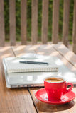 Καυτό φλυτζάνι καφέ στον ξύλινο σταθμό εργασίας Στοκ φωτογραφία με δικαίωμα ελεύθερης χρήσης