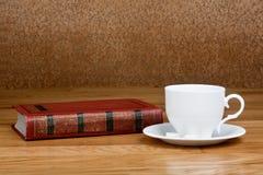 Καυτό φλυτζάνι του φρέσκου καφέ στον ξύλινους πίνακα και το σωρό των βιβλίων Στοκ Φωτογραφία