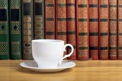 Καυτό φλυτζάνι του φρέσκου καφέ στον ξύλινο πίνακα και ένας σωρός των βιβλίων Στοκ εικόνες με δικαίωμα ελεύθερης χρήσης
