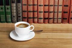 Καυτό φλυτζάνι του φρέσκου καφέ στον ξύλινο πίνακα και ένας σωρός των βιβλίων Στοκ Φωτογραφίες