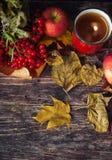 Καυτό φλυτζάνι τσαγιού μια ημέρα φθινοπώρου Επιτραπέζιο υπόβαθρο με τα φύλλα και το α Στοκ φωτογραφία με δικαίωμα ελεύθερης χρήσης