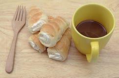 Καυτό ψωμί καφέ και κρέμας στο ξύλινο υπόβαθρο στοκ εικόνες