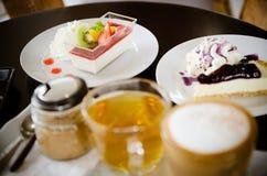 Καυτό cappuccino και καυτό τσάι με τα κέικ Στοκ Εικόνες