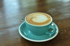 Καυτό latte στον ξύλινο πίνακα στοκ εικόνα