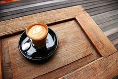 Καυτό piccolo latte που εξυπηρετείται στον πίνακα Στοκ Εικόνα