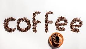 Καφές λέξης που γίνεται από τα φασόλια και τα σιτάρια καφέ στο φλυτζάνι και το πιατάκι Στοκ Εικόνες