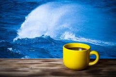 Καφές ή τσάι στο κίτρινο φλυτζάνι στον ξύλινο πίνακα απέναντι από τη θάλασσα wav Στοκ Φωτογραφίες