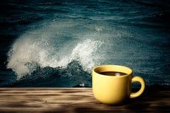 Καφές ή τσάι στο κίτρινο φλυτζάνι στον ξύλινο πίνακα απέναντι από τη θάλασσα wav Στοκ εικόνα με δικαίωμα ελεύθερης χρήσης