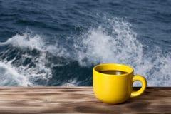 Καφές ή τσάι στο κίτρινο φλυτζάνι στον ξύλινο πίνακα απέναντι από τη θάλασσα wav Στοκ Φωτογραφία