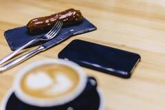 καφές και εύγευστη σοκολάτα ECLAIR σε έναν ξύλινο πίνακα στοκ εικόνες