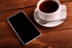 Καφές και κινητό τηλέφωνο Smartphone και ένα φλυτζάνι του espresso σε έναν ξύλινο πίνακα Η συσκευή στοκ φωτογραφίες