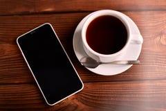 Καφές και κινητό τηλέφωνο Smartphone και ένα φλυτζάνι του espresso σε έναν ξύλινο πίνακα Η συσκευή στοκ φωτογραφία