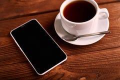 Καφές και κινητό τηλέφωνο Smartphone και ένα φλυτζάνι του espresso σε έναν ξύλινο πίνακα Η συσκευή στοκ φωτογραφία με δικαίωμα ελεύθερης χρήσης