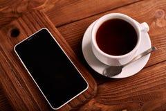Καφές και κινητό τηλέφωνο Smartphone και ένα φλυτζάνι του espresso σε έναν ξύλινο πίνακα Η συσκευή στοκ εικόνες