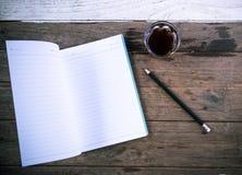Καφές και μολύβι σημειωματάριων στον ξύλινο πίνακα Στοκ Φωτογραφίες