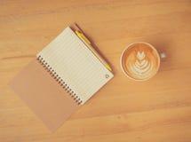 Καφές και σημειωματάριο τέχνης φύλλων latte με τη μάνδρα Στοκ Φωτογραφίες