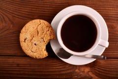 Καφές και σπιτικά μπισκότα με τη σοκολάτα Χειροποίητα μπισκότα σοκολάτας και φλυτζάνι του espresso στον ξύλινο πίνακα στοκ φωτογραφίες