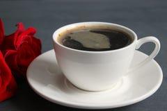 Καφές και τριαντάφυλλα, ακόμα ζωή Μαύρος καφές σε ένα άσπρο φλυτζάνι με ένα πιατάκι στον πίνακα, μια ανθοδέσμη των κόκκινων τριαν στοκ εικόνες