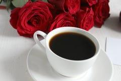 Καφές και τριαντάφυλλα, ακόμα ζωή Μαύρος καφές σε ένα άσπρο φλυτζάνι με ένα πιατάκι στον πίνακα, μια ανθοδέσμη των κόκκινων τριαν στοκ φωτογραφία
