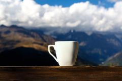 Καφές και τσάι φλυτζανιών με τον ατμό στον ξύλινο πίνακα πέρα από το τοπίο βουνών Στοκ Εικόνες