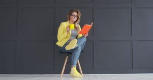 Καφές κατανάλωσης γυναικών και ανάγνωση ενός βιβλίου απόθεμα βίντεο