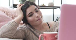 Καφές κατανάλωσης γυναικών και χρησιμοποίηση του lap-top στο σπίτι απόθεμα βίντεο