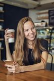 Καφές κατανάλωσης γυναικών με ένα κινητό τηλέφωνο στο χέρι της Στοκ φωτογραφία με δικαίωμα ελεύθερης χρήσης