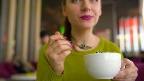 Καφές κατανάλωσης γυναικών με την κτυπημένη κρέμα, σιρόπι σοκολάτας με ένα κουτάλι σε έναν καφέ απόθεμα βίντεο