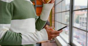 Καφές κατανάλωσης επιχειρηματιών χρησιμοποιώντας το κινητό τηλέφωνο στο γραφείο 4k φιλμ μικρού μήκους