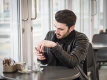 Καφές κατανάλωσης νεαρών άνδρων εξετάζοντας το τηλέφωνο στοκ εικόνες