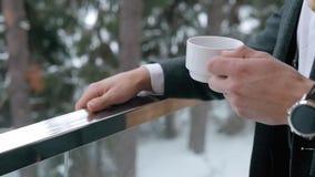 Καφές κατανάλωσης ατόμων σε ένα μπαλκόνι Κλείστε επάνω των χεριών με το άσπρο φλιτζάνι του καφέ φιλμ μικρού μήκους