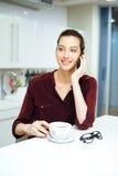 Καφές κατανάλωσης γυναικών και ομιλία στο κινητό τηλέφωνο στην κουζίνα στοκ φωτογραφία με δικαίωμα ελεύθερης χρήσης